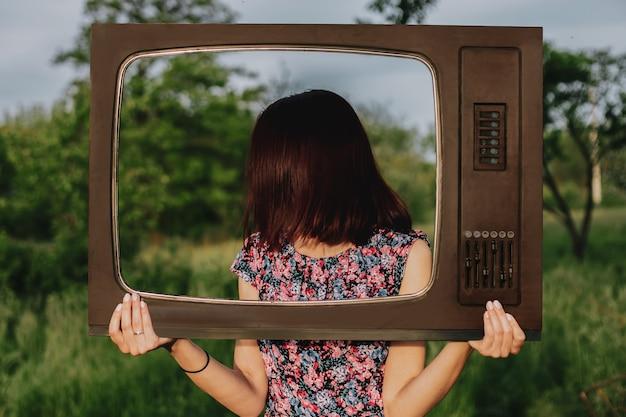 女の子は屋外の庭でビンテージテレビで自分自身をフレームします、顔はありません