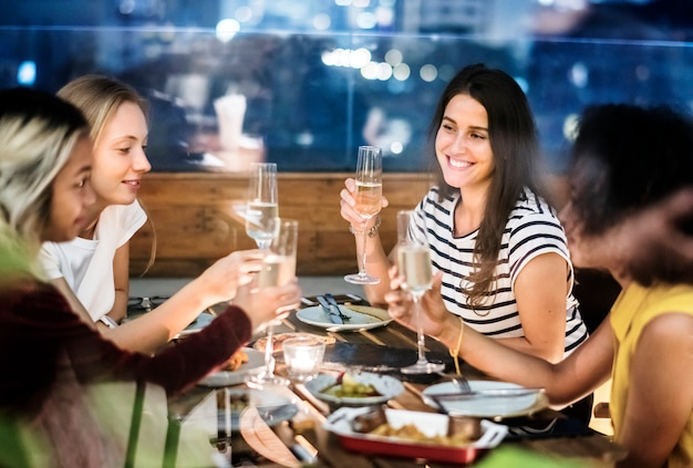 Girl friends having a dinner together at a rooftop bar