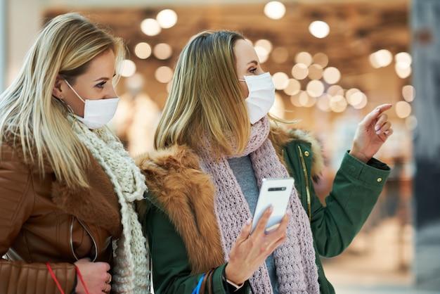 マスクコロナウイルスのコンセプトを身に着けて一緒に買い物をするスマートフォンを持つガールフレンド