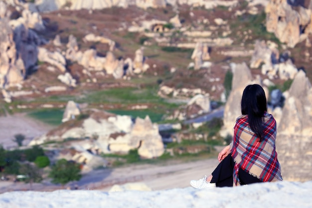 Девушка с холма смотрит на вулканические породы в долине каппадокии