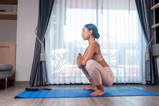 A girl from a mixed race, posing while standing in a frog pose and enjoys stretching
