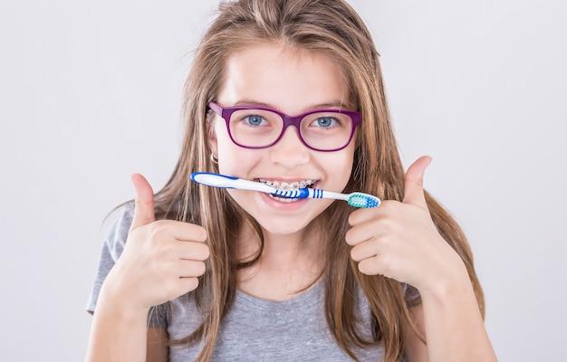 칫 솔이 엄지손가락을 위로 손 기호 제스처를 만드는 치과 교정기에서 소녀. 치열 교정 및 치과 의사 개념입니다.
