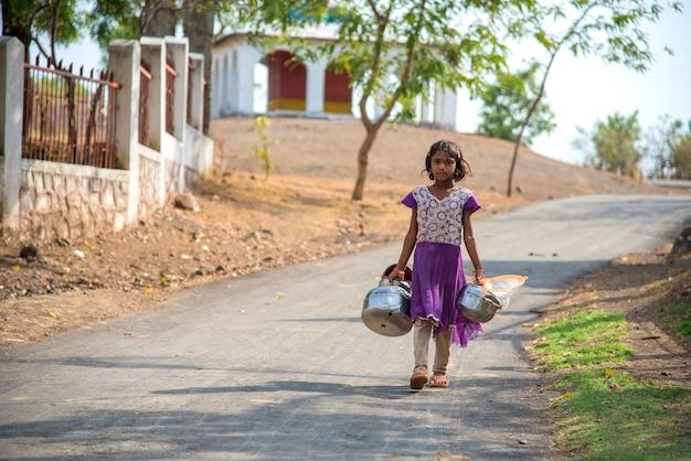 우물에서 식수를 모으기 위해 걷는 마을의 소녀.