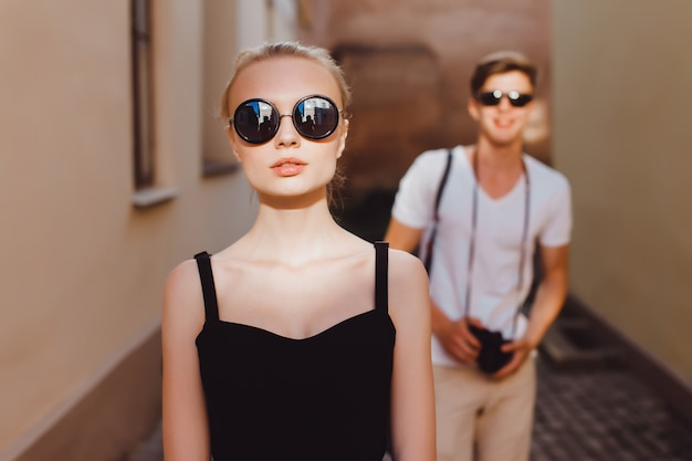 Girl in front and a boy behind with a camera in hands