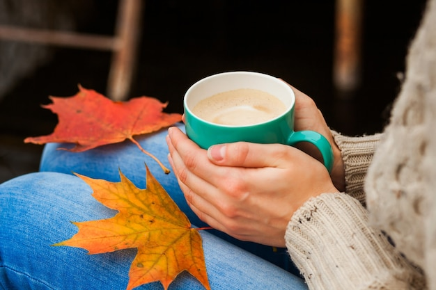 The girl froze and holding a hot cup of coffee in hand. autumn leaves. blue, red, yellow cold.