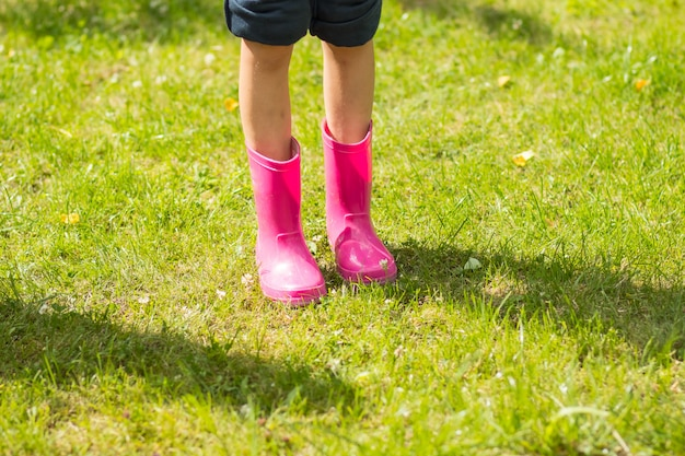 Girl in funny rubber boots standing in the garden after rain.