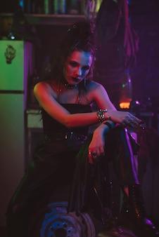Girl in a futuristic cyberpunk costume smokes a cigarette with a neon light in the garage. steampunk style. futuristic post-apocalyptic style