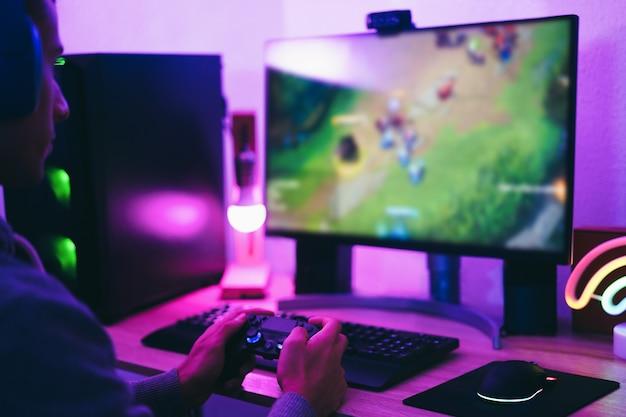 Девушка-геймер играет в онлайн-стратегию с помощью гарнитуры виртуальной реальности - мягкий фокус на правой руке