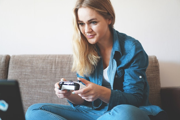 女の子のゲーマーは、目の前の画面を見ながらワイヤレスゲームパッドで遊んでいます。若いブロンドの女の子は微笑んで、ビデオゲームコンソールを楽しんでいます。