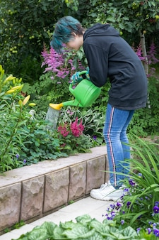A girl in the garden waters flowers from a watering can gardening hobby small business landscaping