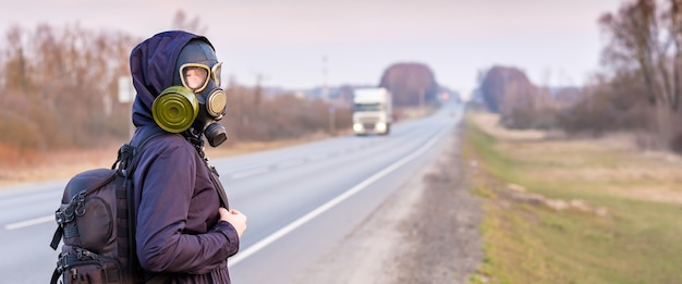 A girl in a gas mask hitchhikes and walks along the side of the road past passing cars