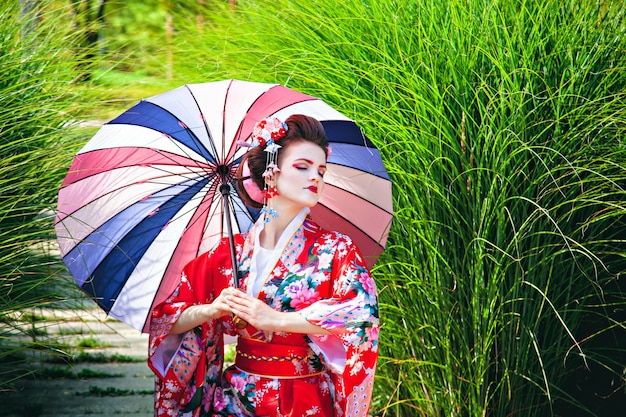 Girl in geisha costume with fancy make-up in the garden with an umbrella