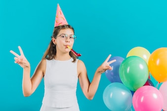 Girl gesturing peace sign near colorful balloons on turquoise colored background