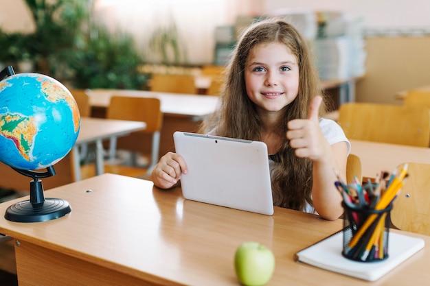 Девушка gesturing большой палец вверх с планшета