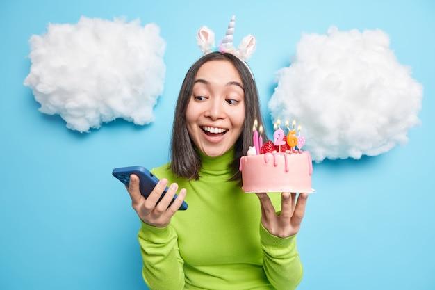 소녀는 스마트 폰에서 축하 메시지를받으며 불타는 촛불로 축제 맛있는 케이크를 보유하고 행복한 표현이 녹색 폴로 넥을 착용합니다.