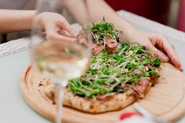 소녀는 손에 pinsa romana를 가져옵니다. 이탈리아 미식가 요리. 스크로키아렐라. 페퍼로니, 토마토, 치즈, 마이크로그린을 곁들인 핀사.