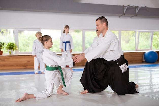 Девушка готовится к занятиям айкидо со своим тренером
