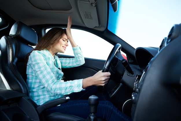 Girl girl wearing blue shirt sitting in new automobile, stuck in traffic, depressed, accident, engine problems, woman driver.