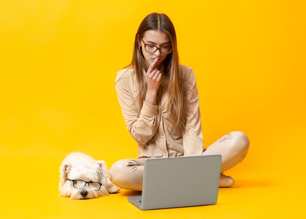A girl a girl with a dog works at a laptop on a yellow background.with a dog works at a laptop on a yellow background. high quality photo