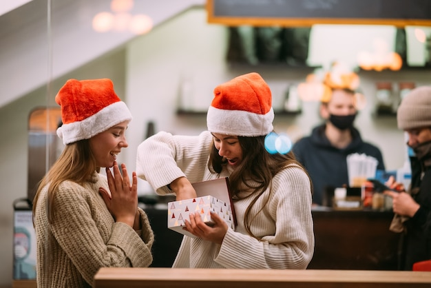 The girl gives a gift to her female friend at the cafe