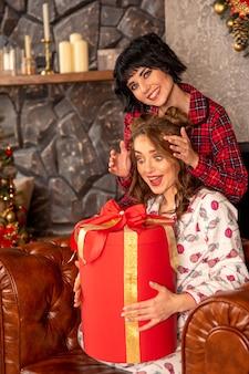 Девушка делает рождественский подарок своей девушке. подруга выглядит удивленной и счастливой, потому что в ее руках большой красный подарок с золотыми лентами.