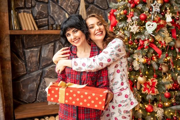 Девушка дает рождественский подарок своей девушке. они обнимаются возле елки и выглядят очень счастливыми.
