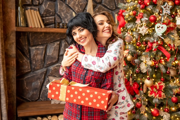 Девушка делает рождественский подарок своей девушке. они обнимаются возле елки и выглядят очень счастливыми.