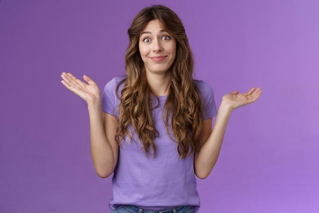 Ragazza che non si preoccupa. donna caucasica carina dai capelli ricci spensierata spensierata che alza le mani allargando le mani lateralmente sorridendo indifferente niente da dire scuotere la testa interrogato all'oscuro sfondo viola