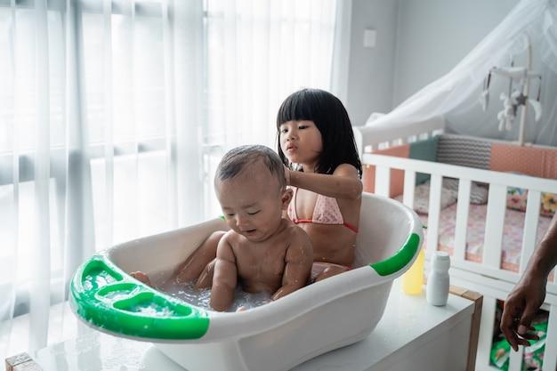 Девушка дает ванну своему младшему брату на тазике