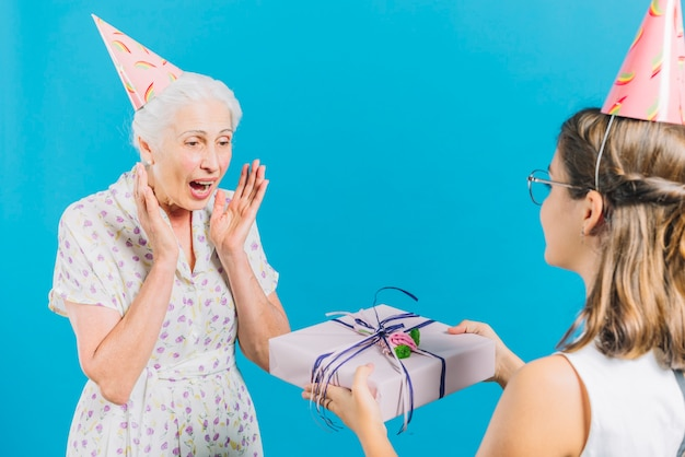 Girl giving birthday gift to surprised grandmother on blue backdrop