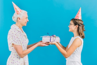 Girl giving birthday gift to her grandmother on blue background