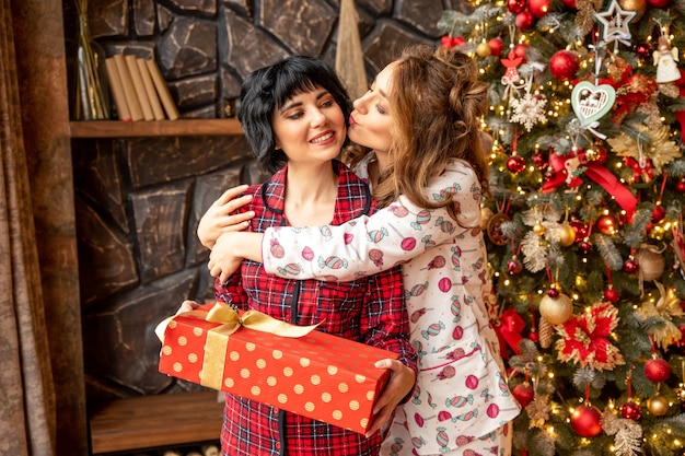 Girl giving a christmas present to her girlfriend. girl kissing her friend near christmas tree.