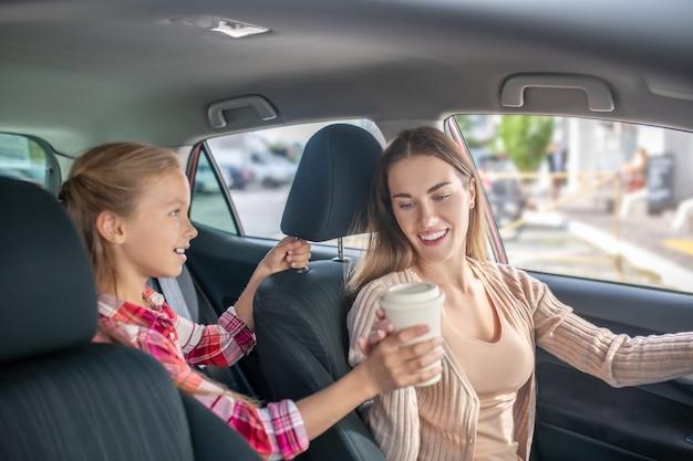 ハンドルに座っている彼女のお母さんにコーヒーカップを与える女の子