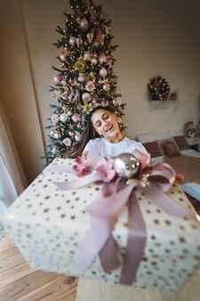 Girl giving a gift on the background of a christmas tree