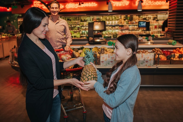 Girl giving pineapple to her mother at grocery store