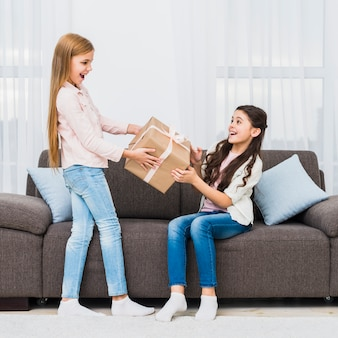 Girl giving present to her surprised friend sitting on sofa in the living room