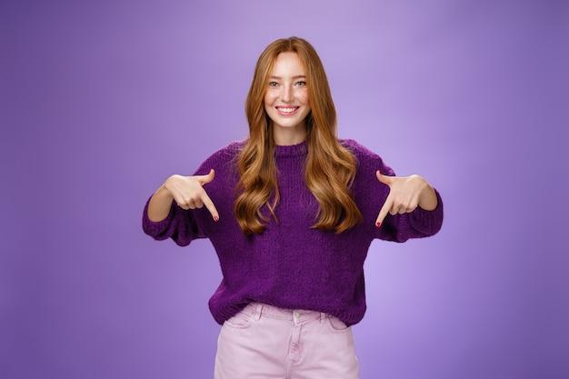 Девушка дает рекомендацию посетить место, указывая вниз и дружелюбно улыбается с довольной и приятной улыбкой. портрет привлекательной рыжей женской модели в фиолетовом теплом свитере повышая космос экземпляра.