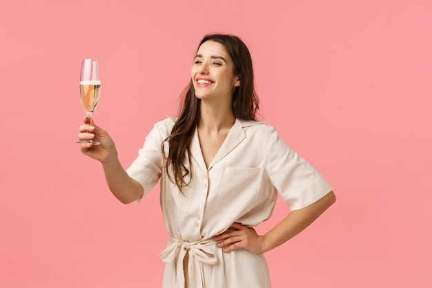 Girl giving a speech during bachelorette party. cheerful and happy smiling carefree young woman in dress, raising glass champagne laughing and grinning, congratulating with birthday, pink wall