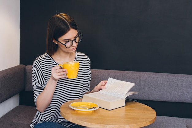 Girl in glasses reading a book in a coffee shop