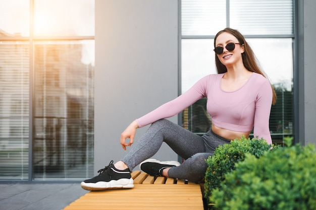 Girl in glasses sits on a bench