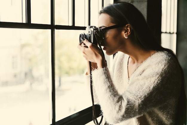 Girl in glasses takes a photo standing before a bright window