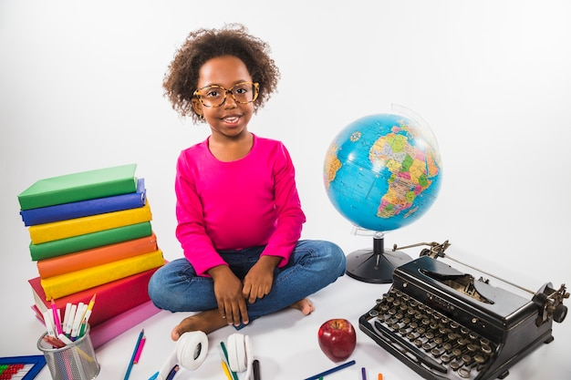 Girl in glasses with study tools in studio