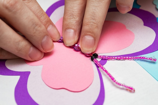 The girl glues the elements of the application with hot glue