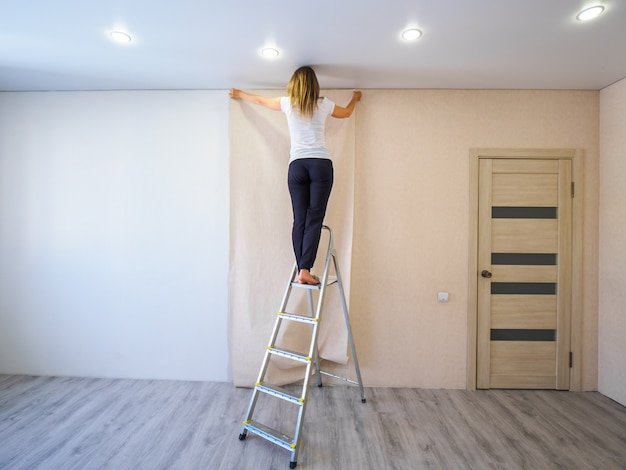 Girl glues a strip of wallpaper from the step ladder