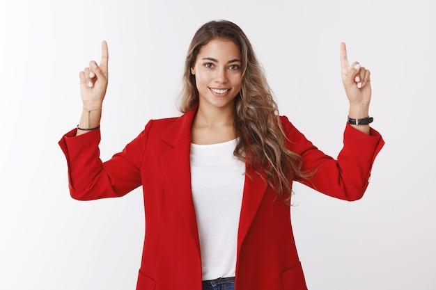 Цель девушки занять первое место. уверенная в себе и решительная великолепная женщина-предприниматель 25-х годов в красной куртке поднимает руки, указывая указательным пальцем вверх, показывая пространство для копирования, улыбаясь, повезло, уверенно