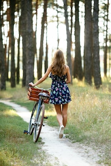 Girl goes on a bicycle path in the woods