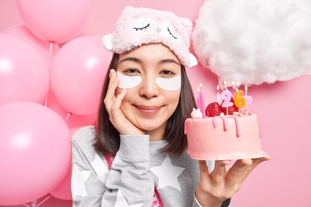 Girl going to blow candles on cake and make wish prepares for party and celebration dressed in pajama decorates room with balloons