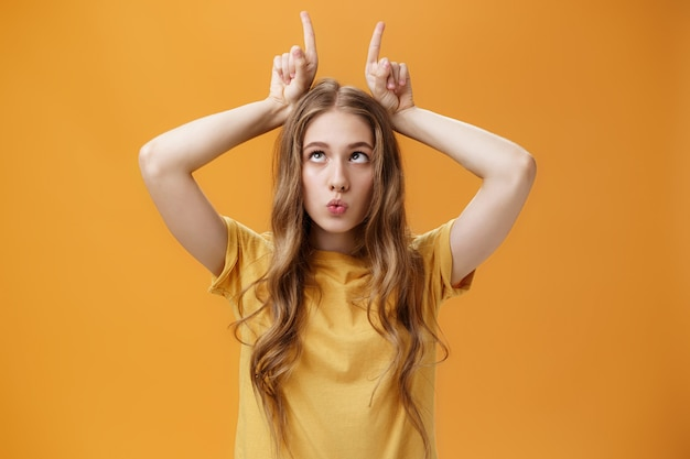 Девушка сходит с ума от скуки, корчит причудливые смешные рожицы, дурачится, прищуривается, держит указательные пальцы на голове, как рога, высунув язык, и складывает губы, подражая оранжевому фону.