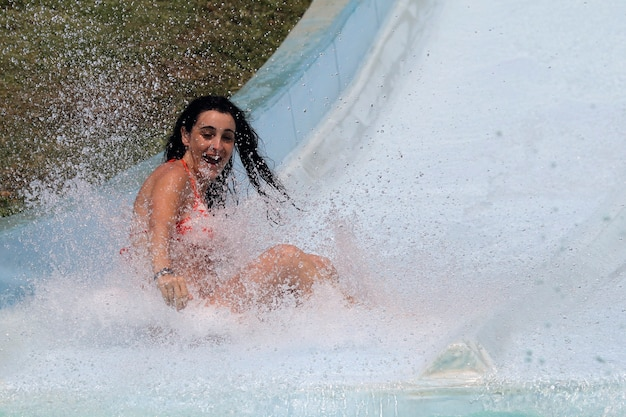Girl going down and enjoying water slide in water park
