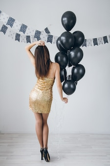 Girl in a gold dress with black balloons
